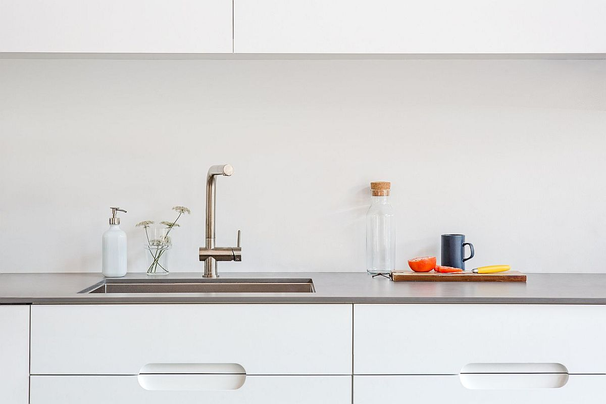 Ergonomic kitchen workstation with white cabinets and polished countertop