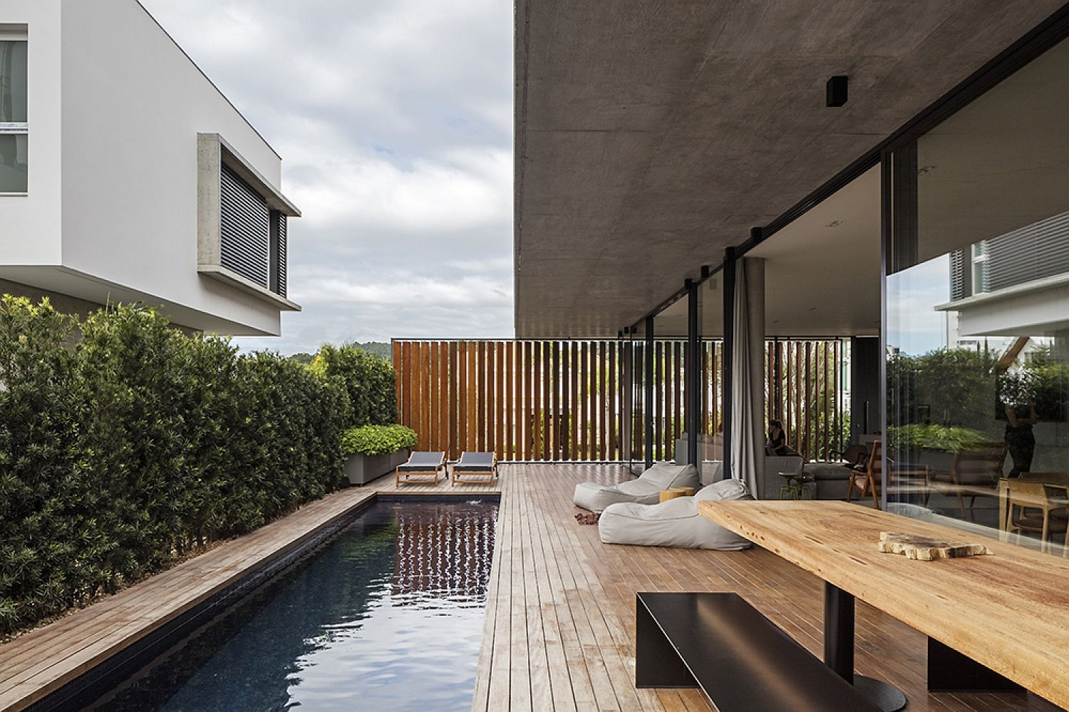 Expansive wooden deck and pool connecetd with ground level living area