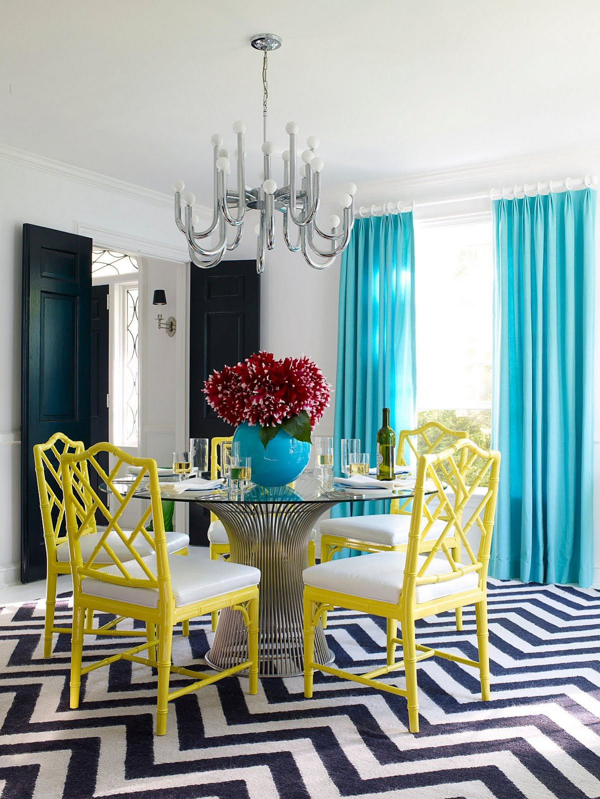 Exquisite dining room with light blue drapes, yellow chairs and a snazzy chevron pattern rug
