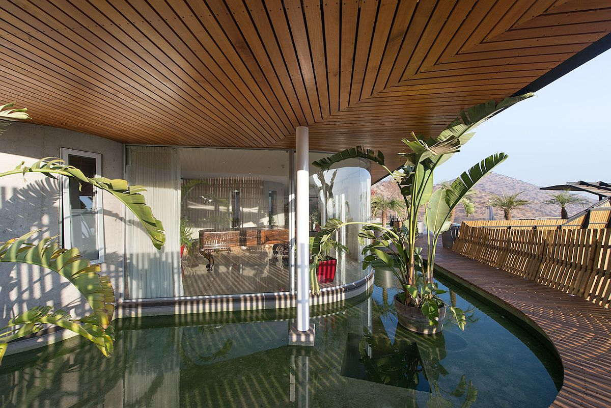 Exquisite wooden deck and reflecting pond around the Chilean home help regulate temperature