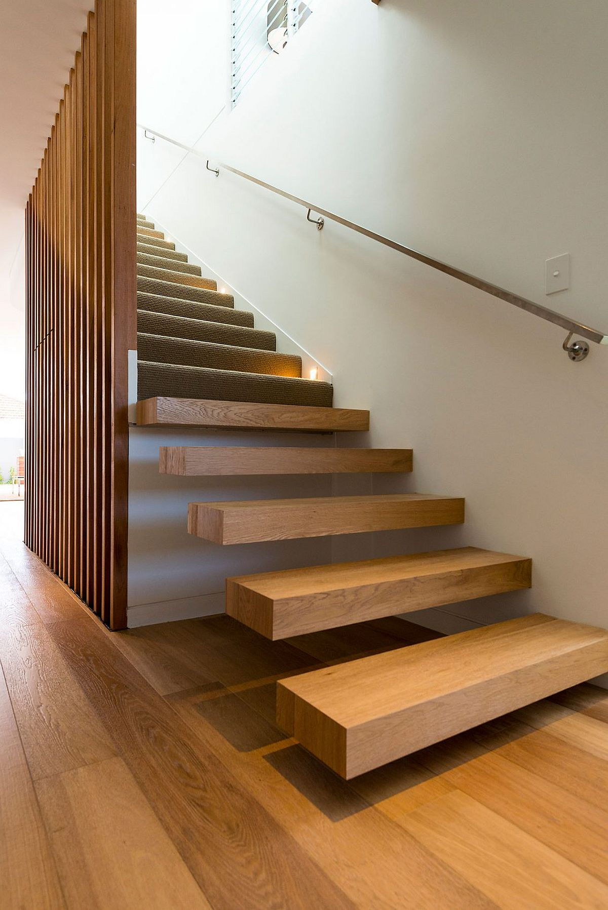 Floating wooden staircase with wooden slats inisde the contemporary home