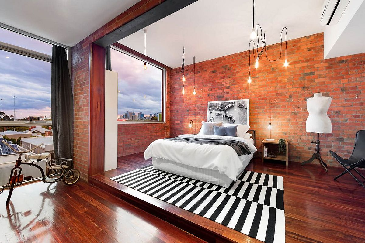 Industrial bedroom with brick walls and ample lighting