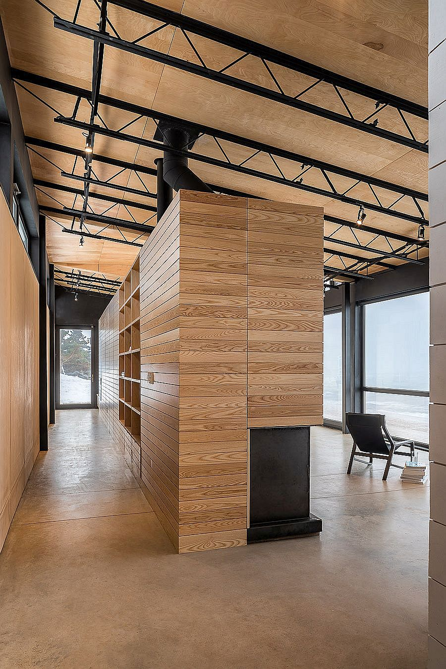 Interior clad in wood with metallic frame at the Canadian coastal home