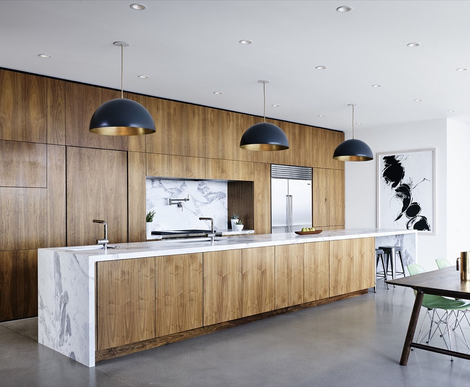 Kitchen island in wood with marble countertop and dark pendants above