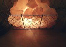 Lit-up-salt-crystal-pieces-within-a-wire-basket-create-a-unique-salt-lamp-installation-217x155