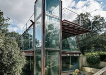 Metal-and-glass-structure-on-forest-clearing-overlooks-a-small-waterfall-217x155