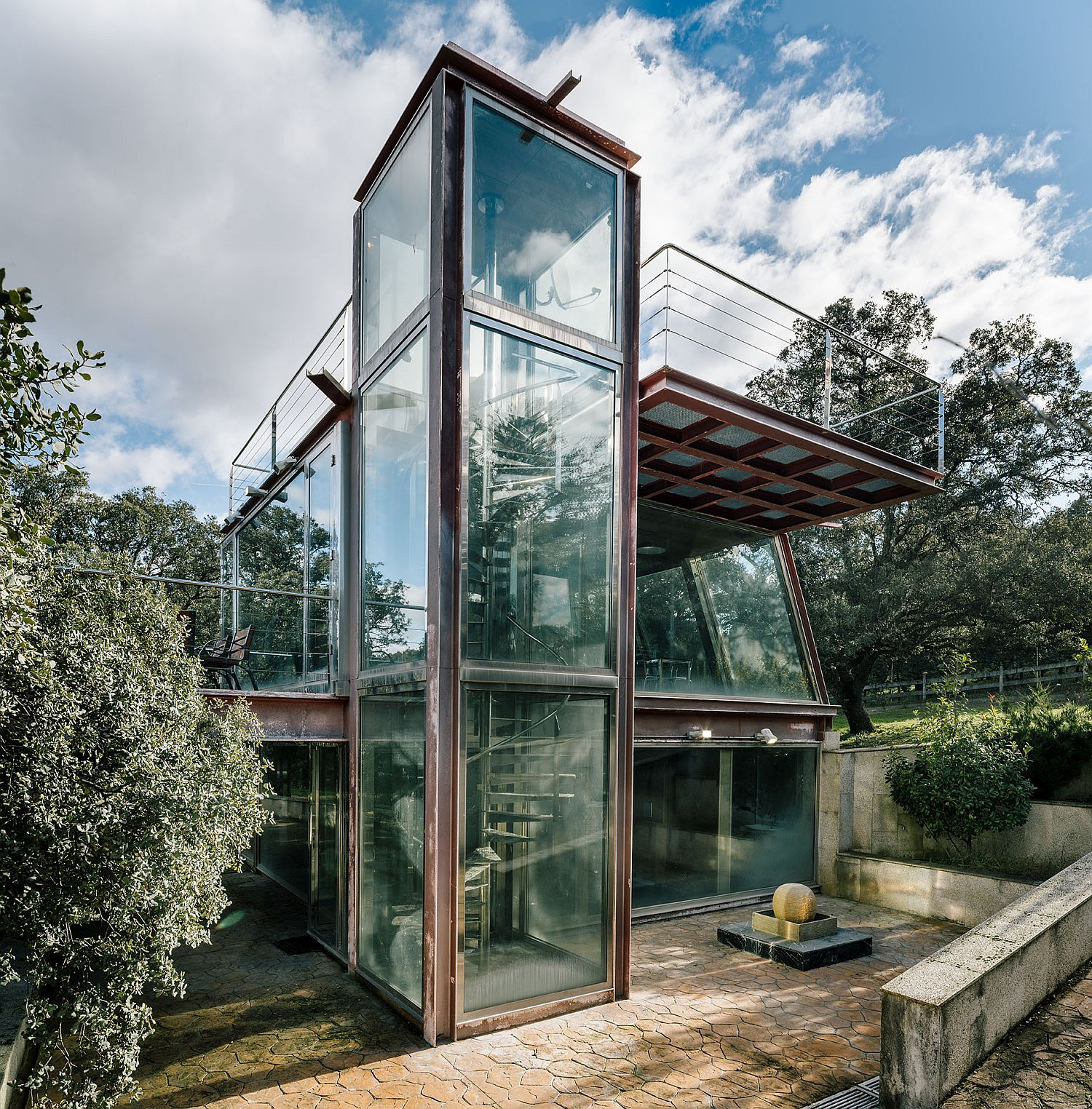 Metal-and-glass-structure-on-forest-clearing-overlooks-a-small-waterfall