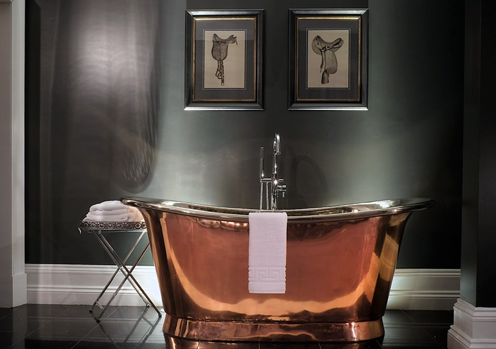 Polished and shiny copper bathtub thrives in a dark bathroom