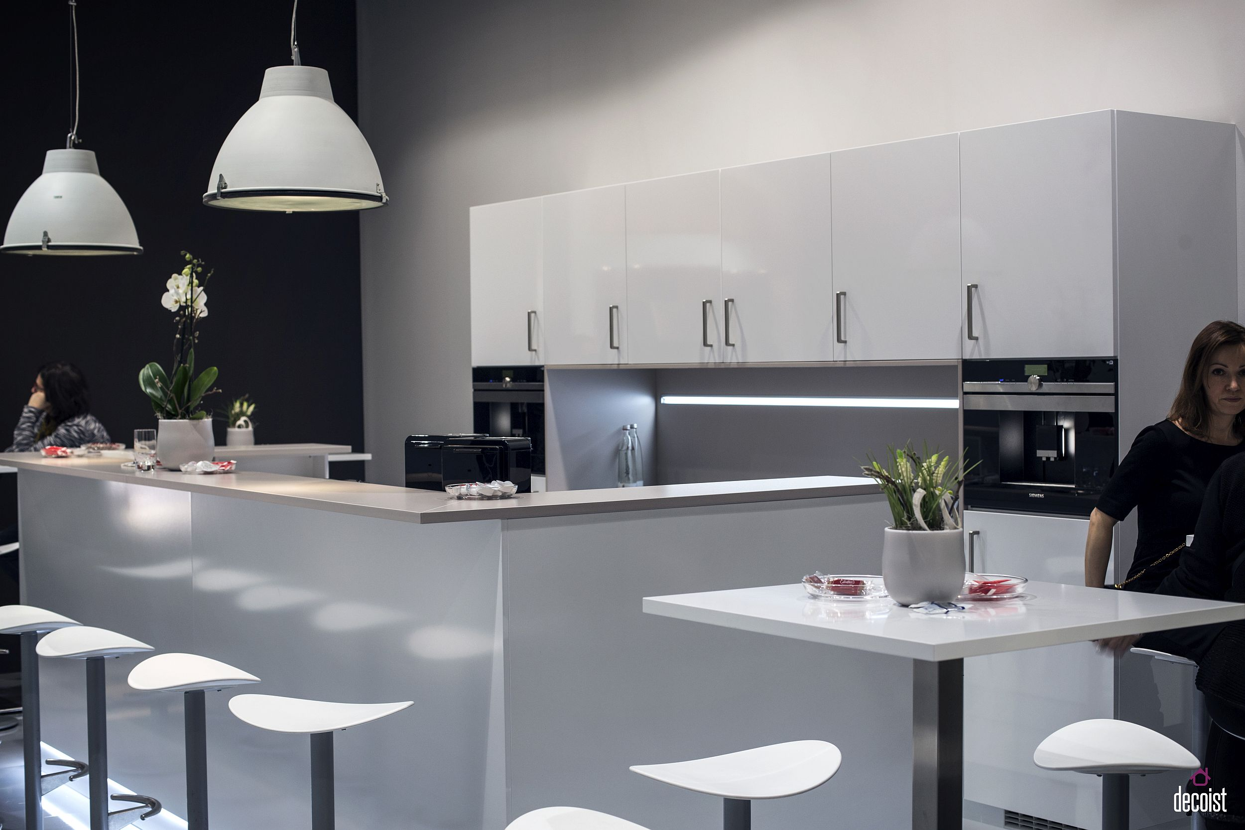 Slim breakfast bar top along with additional sitting and counter space in the white kitchen