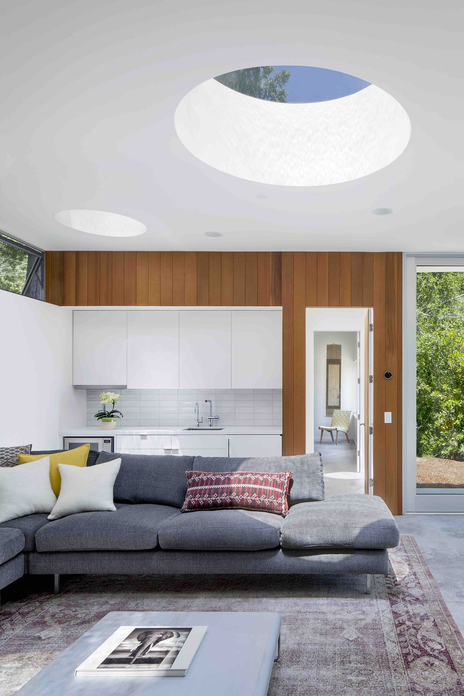 Smart interior of the guestouse with gray sectional and white backdrop