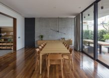 Spacious-dining-room-with-concrete-and-glass-walls-along-with-wooden-flooring-217x155