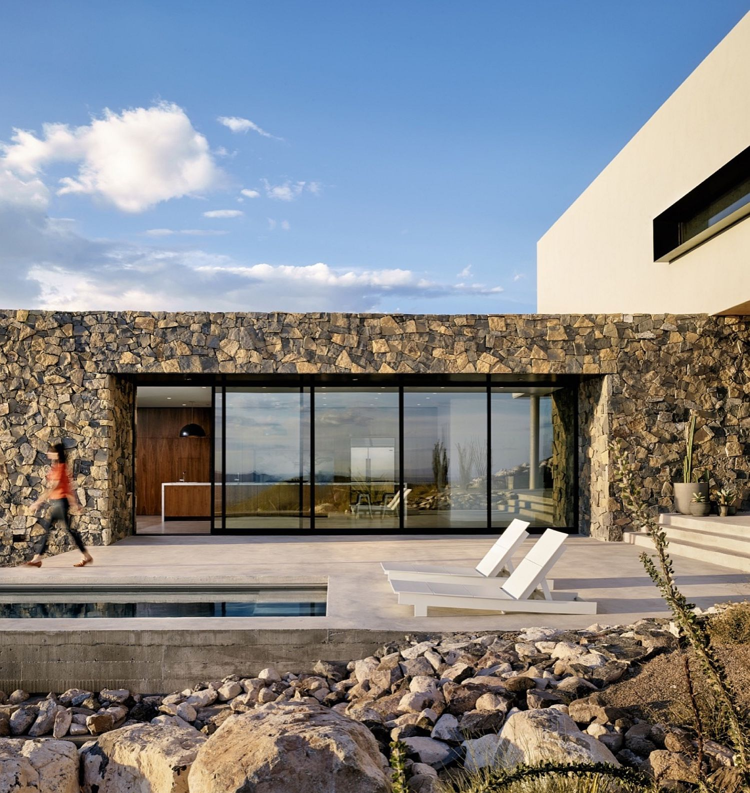 Stone exterior of the contemporary home with sliding glass walls