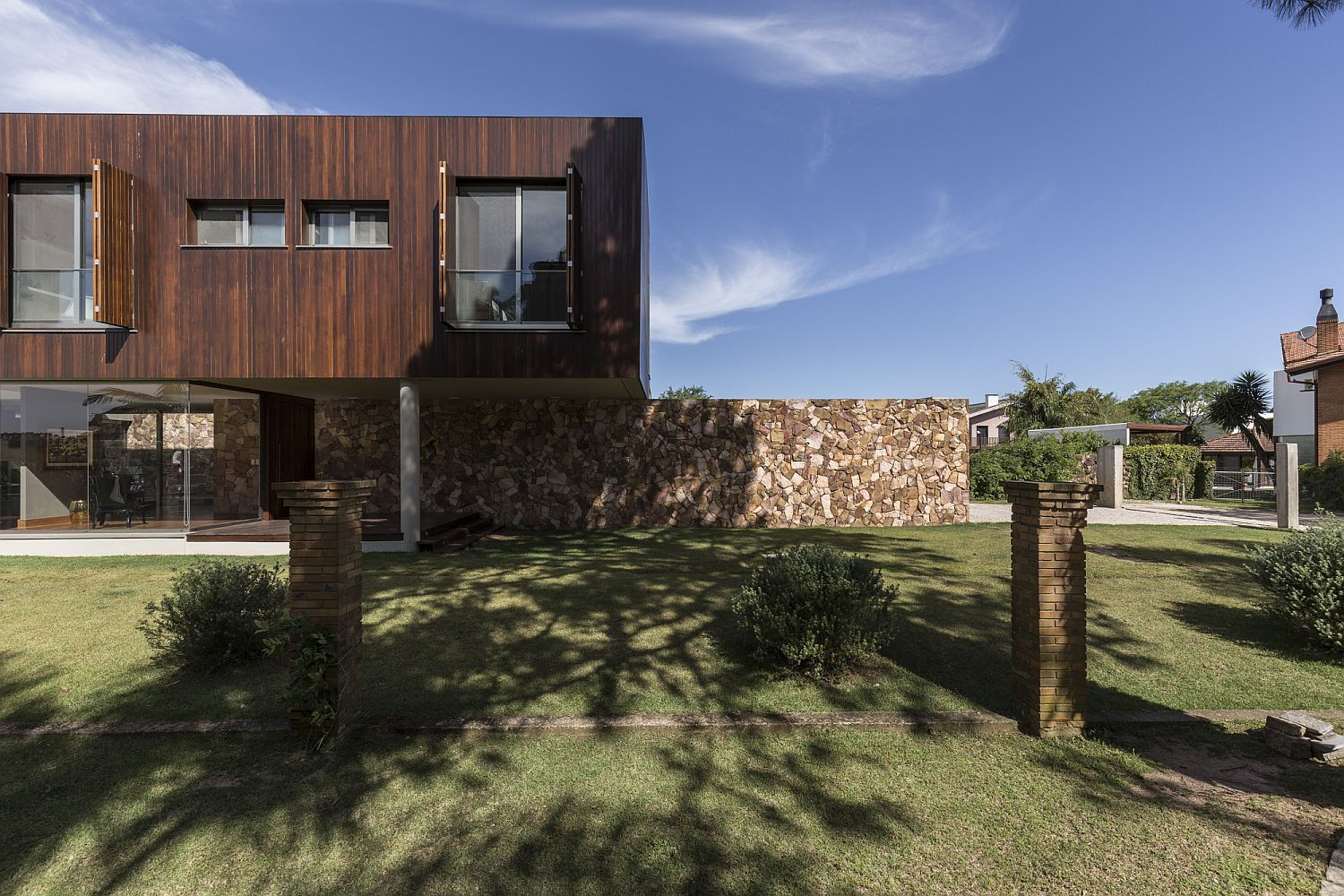Stone wall made from local stone with cantilevered structure of the home above Breezy Natural Vibe: Cantilevered Brazilian Home Captivates with River Views
