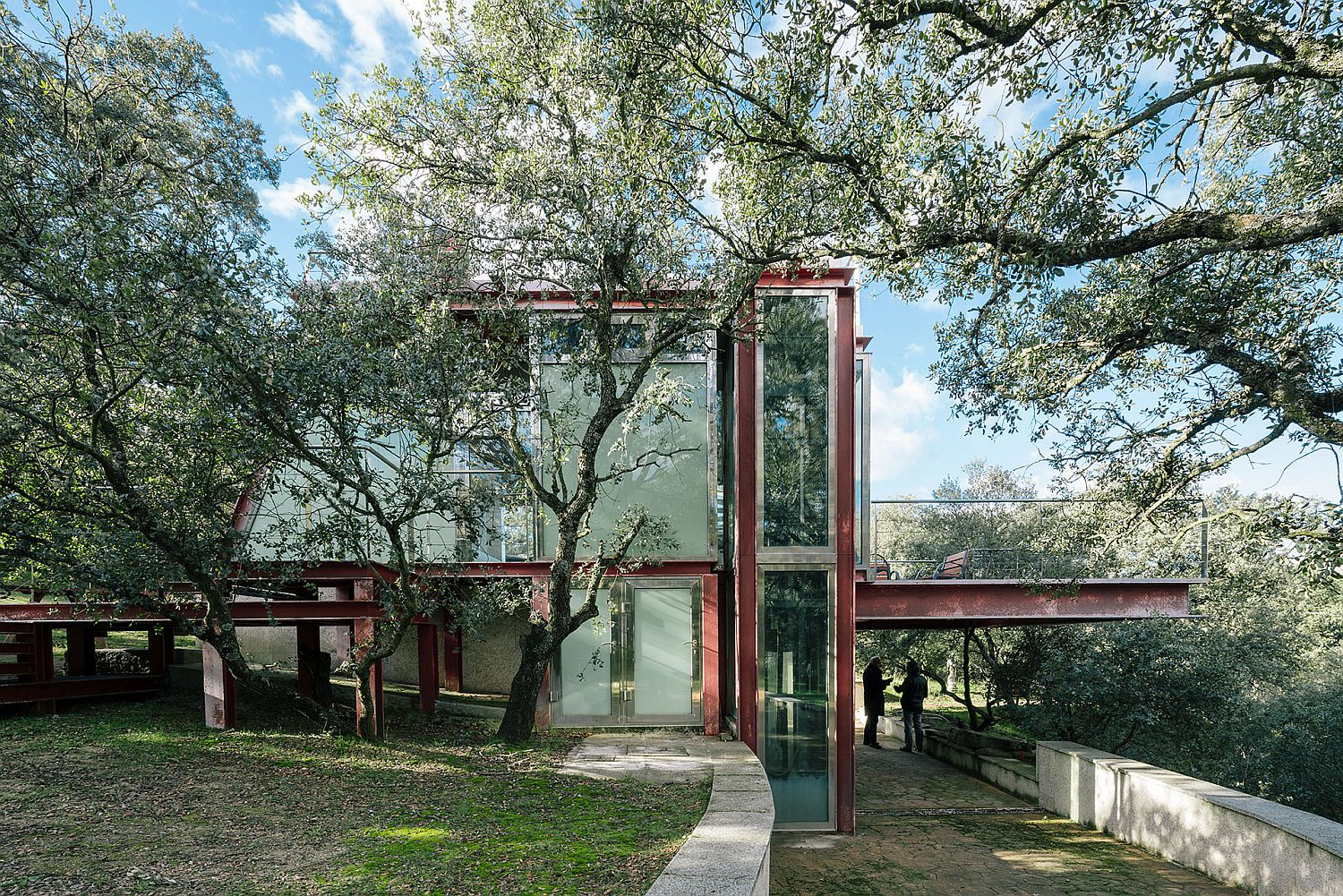 Stunning glass and metal design of The Hidden Pavilion surrounded by forest canopy