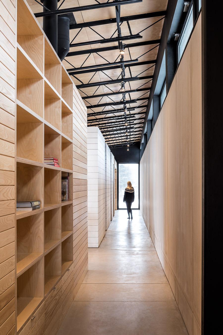 Tall custom shelves in wood shape the interior