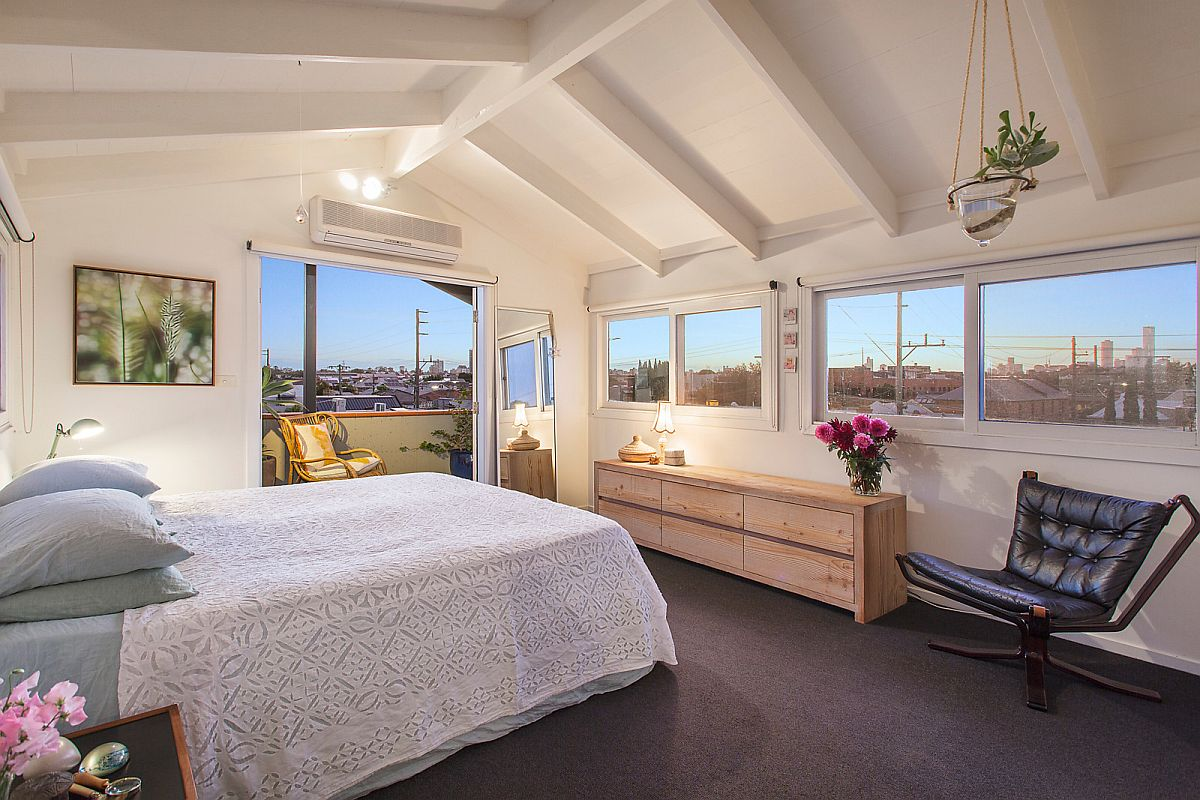 Tranquil and modern bedroom in white with a view of Melbourne's cityscape