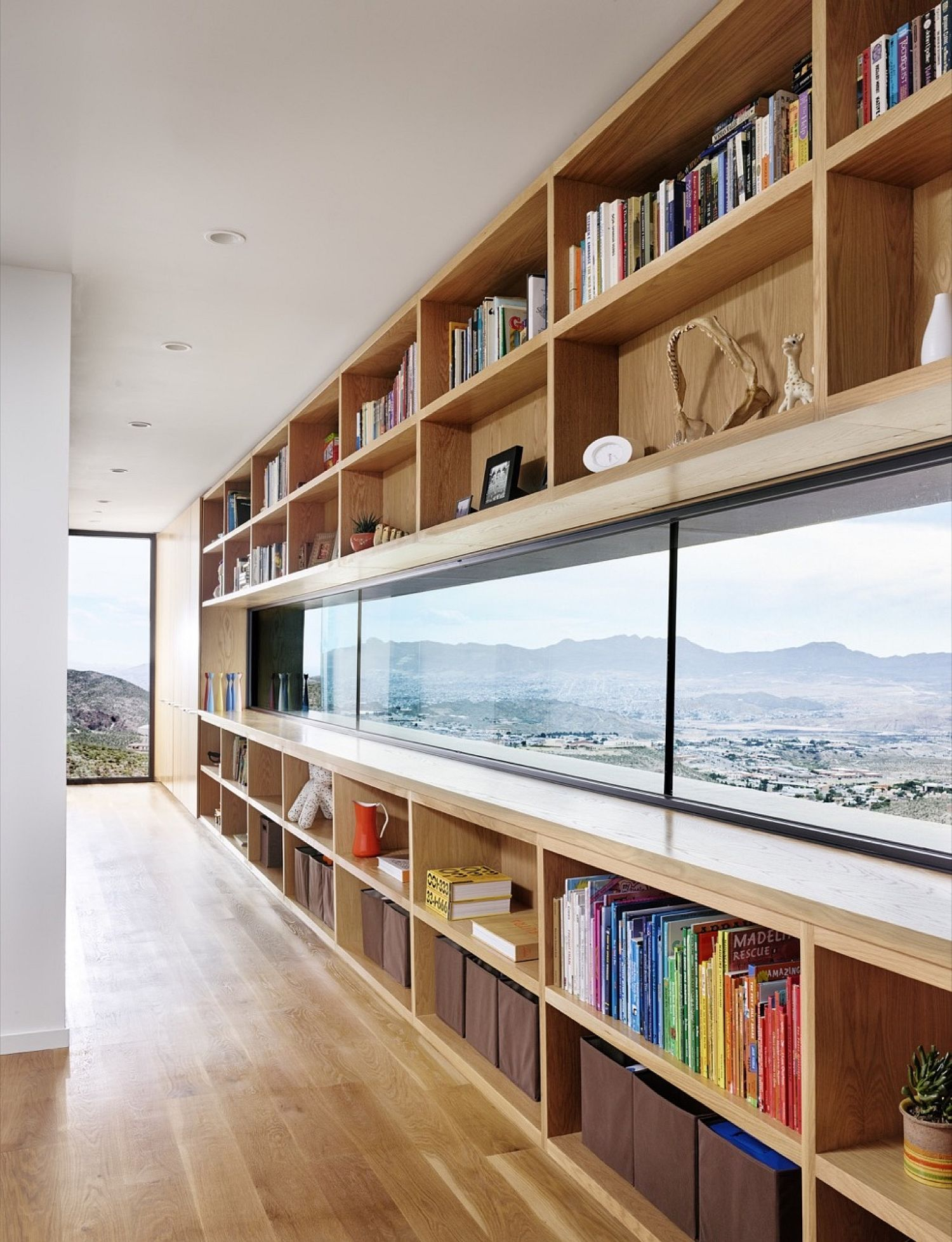 Wall of open shelves and long windows combines storage with captivating views