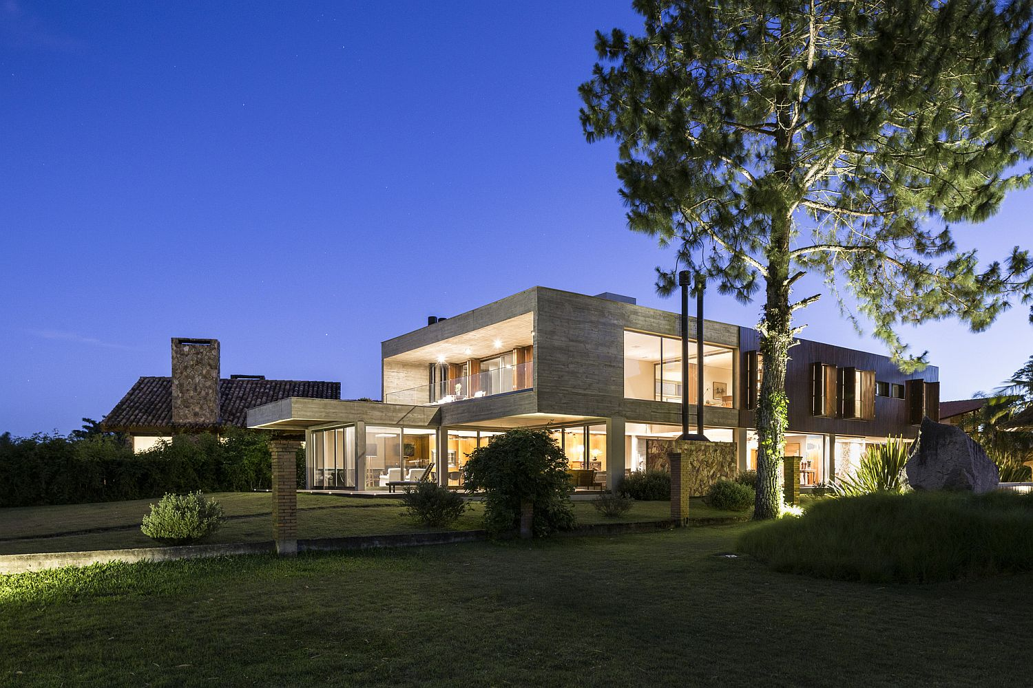 Warm lighting and green landscape elevate the style quotient of the Brazilian home
