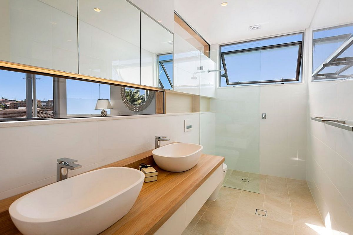 White-modern-bathroom-with-floating-vanity-wooden-countertop-and-twin-sinks