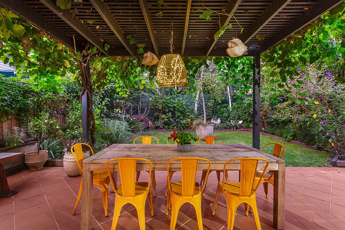 Wooden table and bright yellow chairs for alfresco dining on the terrace
