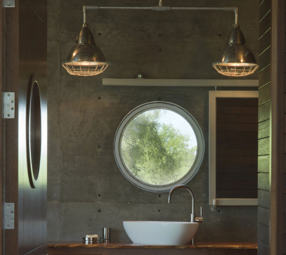 A concrete bathroom with a round window