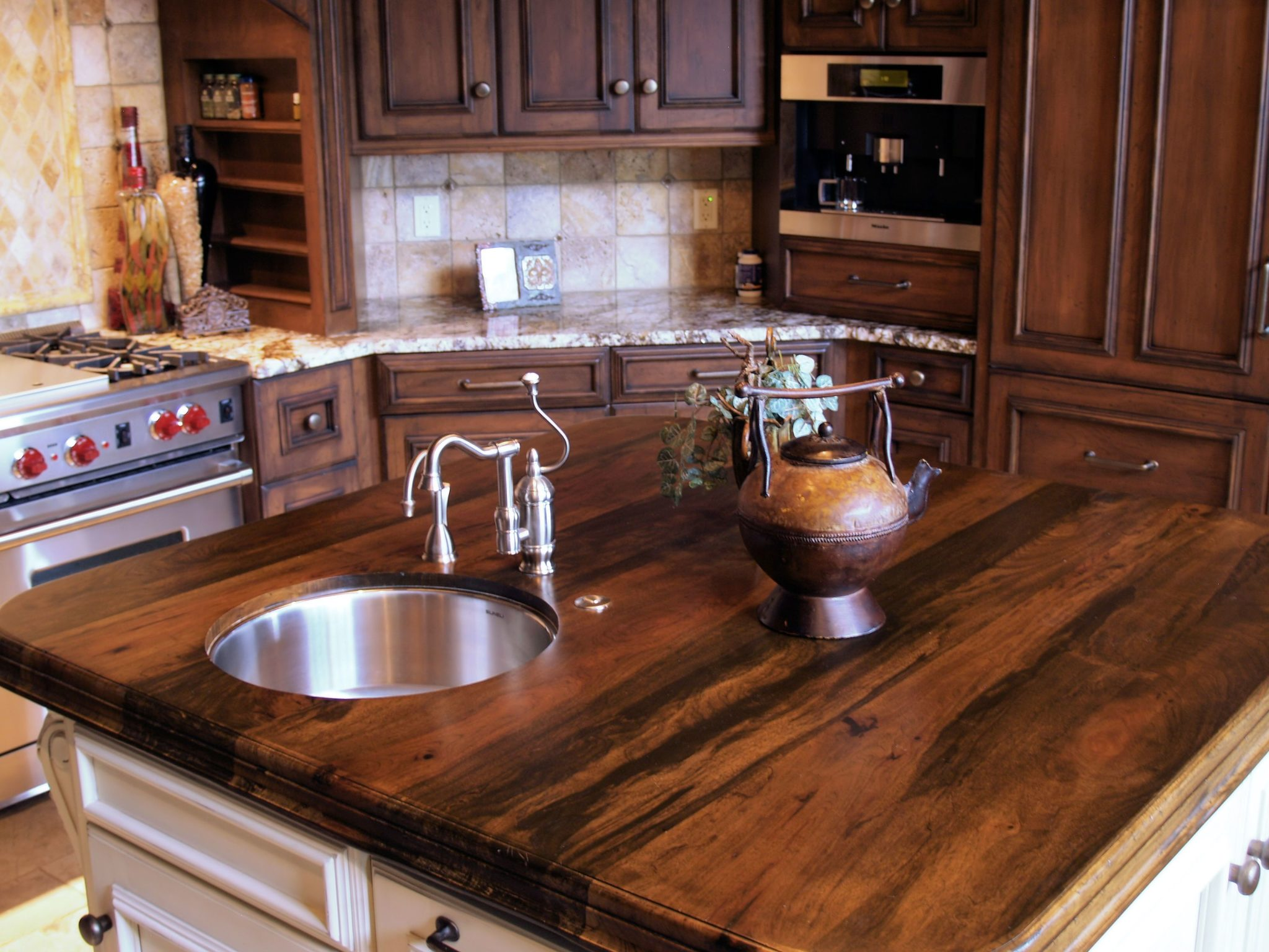 A kitchen island with a dark wooden countertop is the ultimate centerpiece