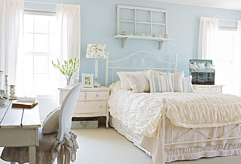 A white antique bedroom with a light blue wall