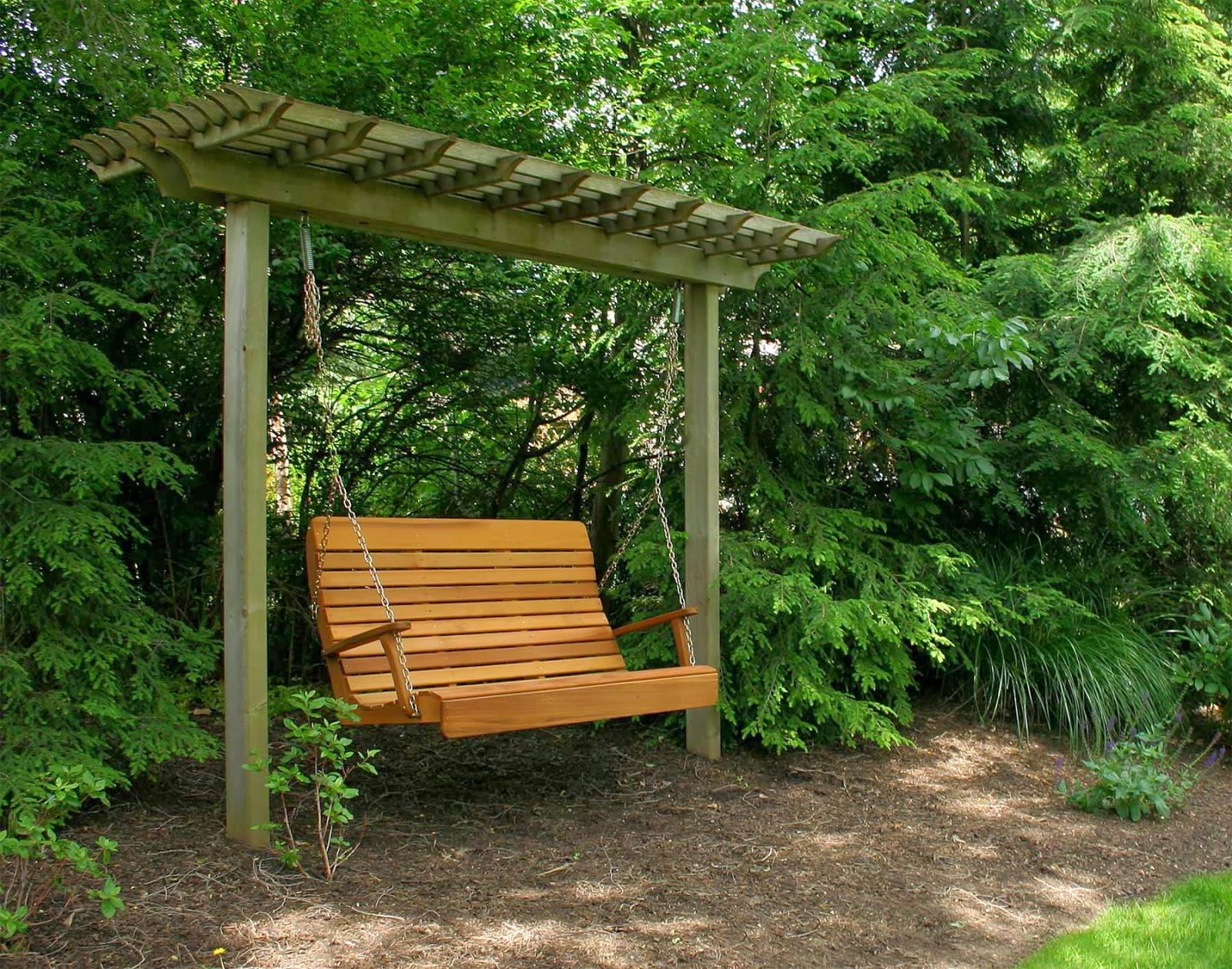 A wooden swing inside a bushy garden