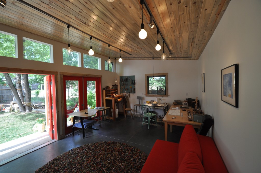 Art studio with a gentle shade of wood and vibrant red elements