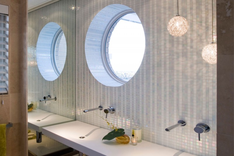 Bathroom with a round window right above the sink
