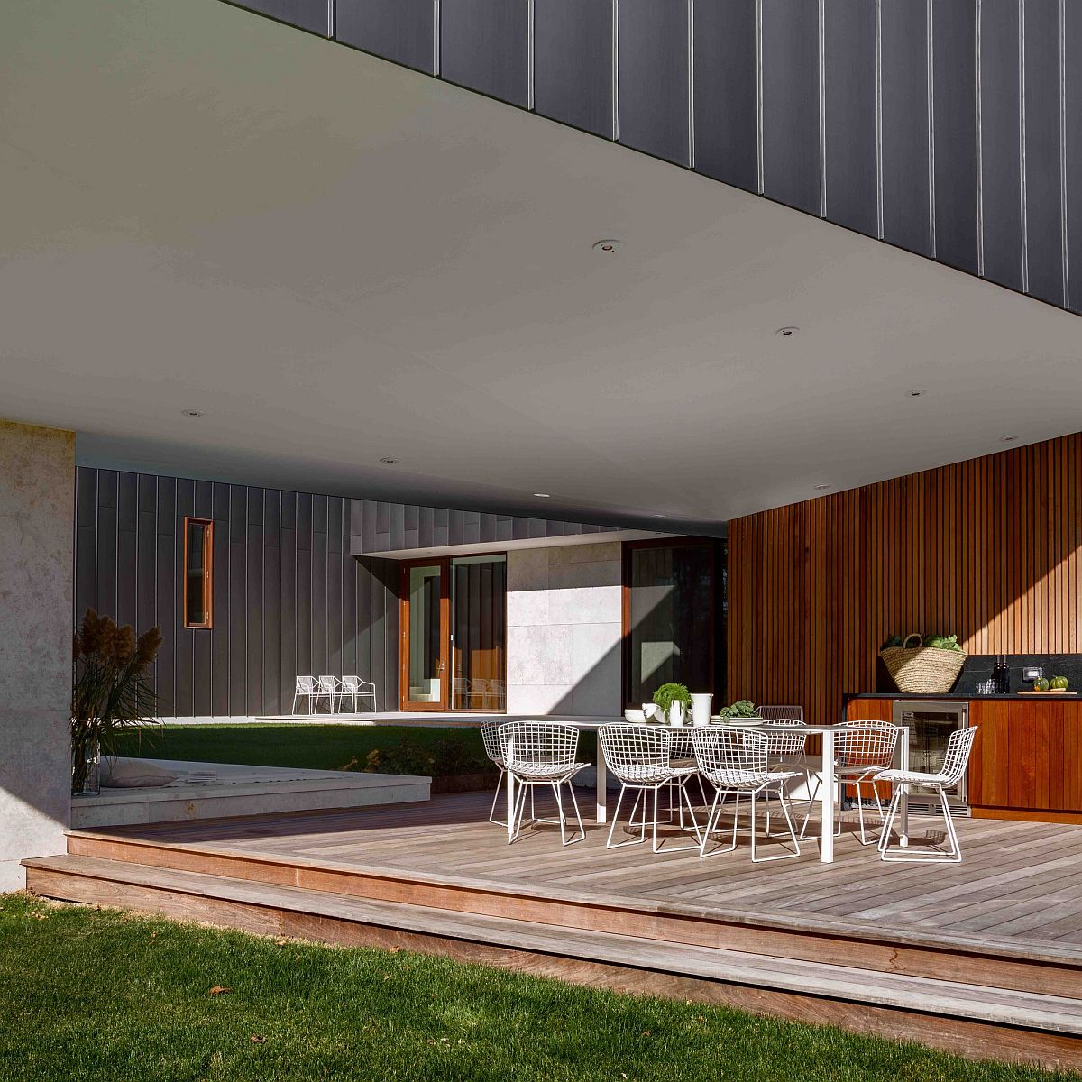 Cantilevered structure of the home offers shade for the outdoor dining and barbecue zone