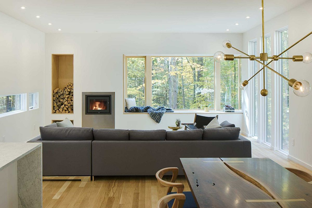 Comfy window seat creates a space-savvy redaing nook with a view of the forest outside