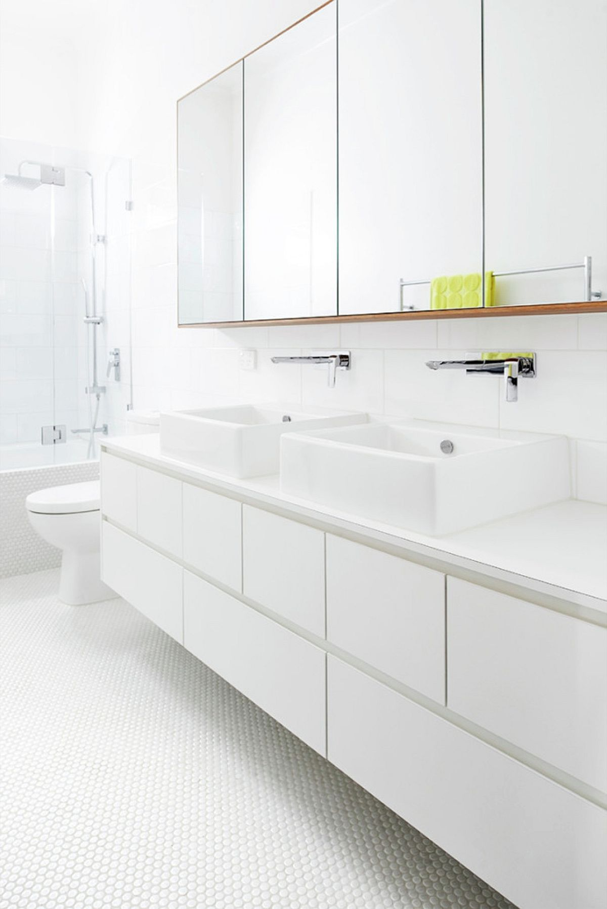 Contemporary all-white bathroom with penny tile flooring