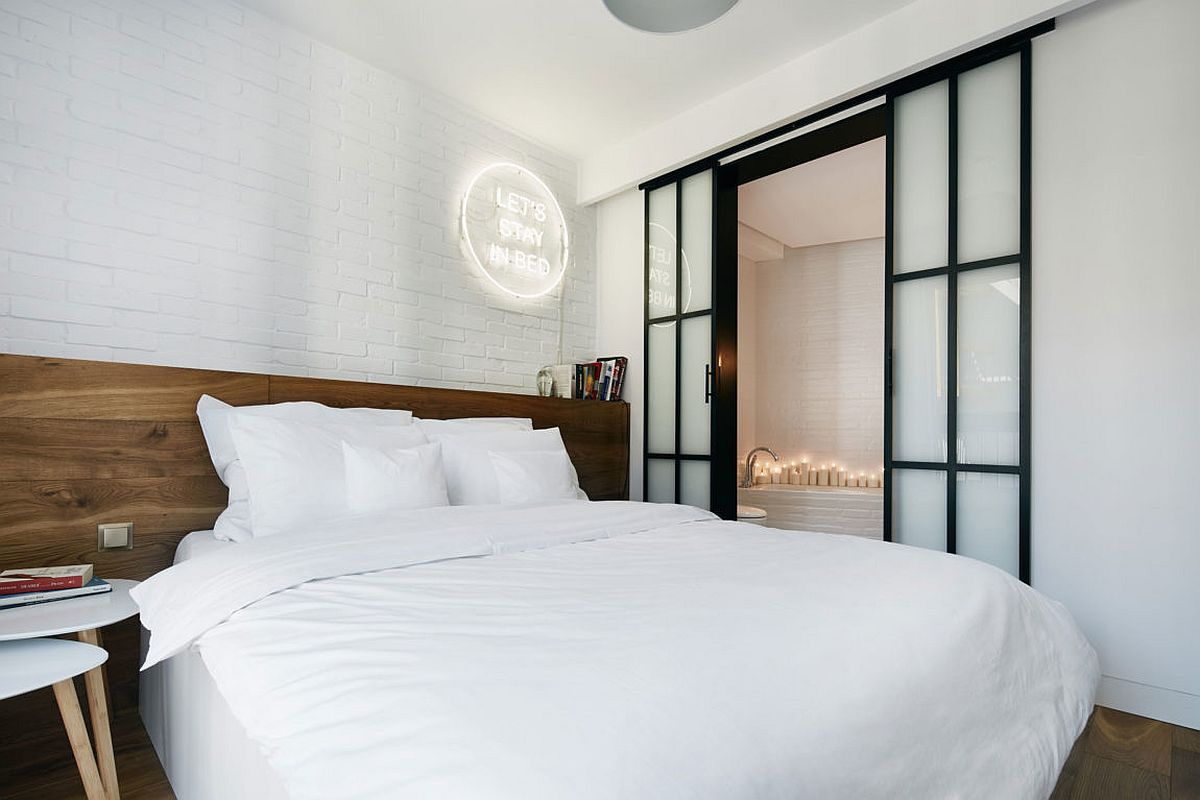 Contemporary bedroom in white allows the wooden headboard to stand out visually