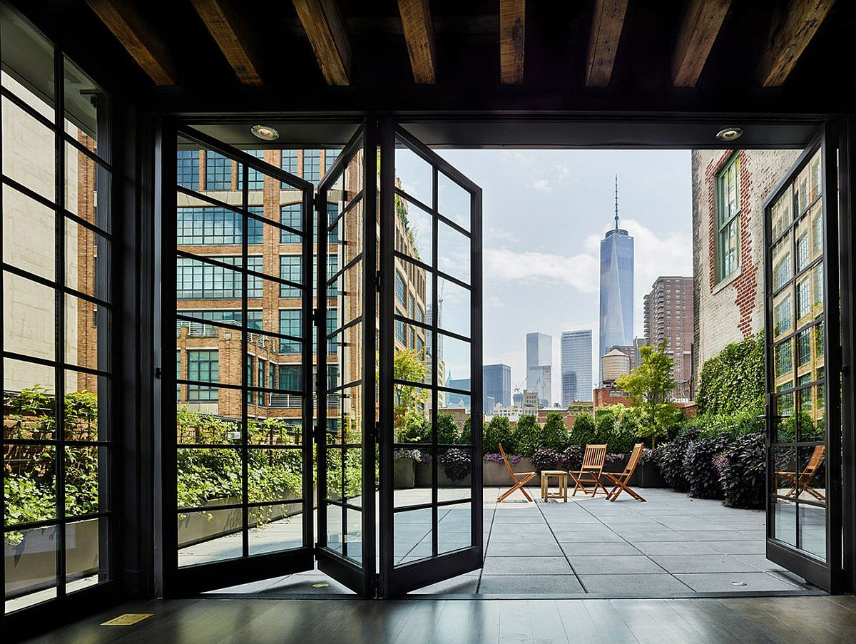 View in gallery folding framed glass doors give the new york pethouse industrial charm