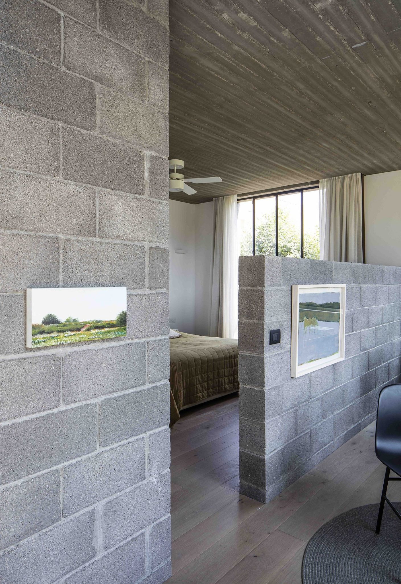 Half-wall delineates the bedroom from the master bath
