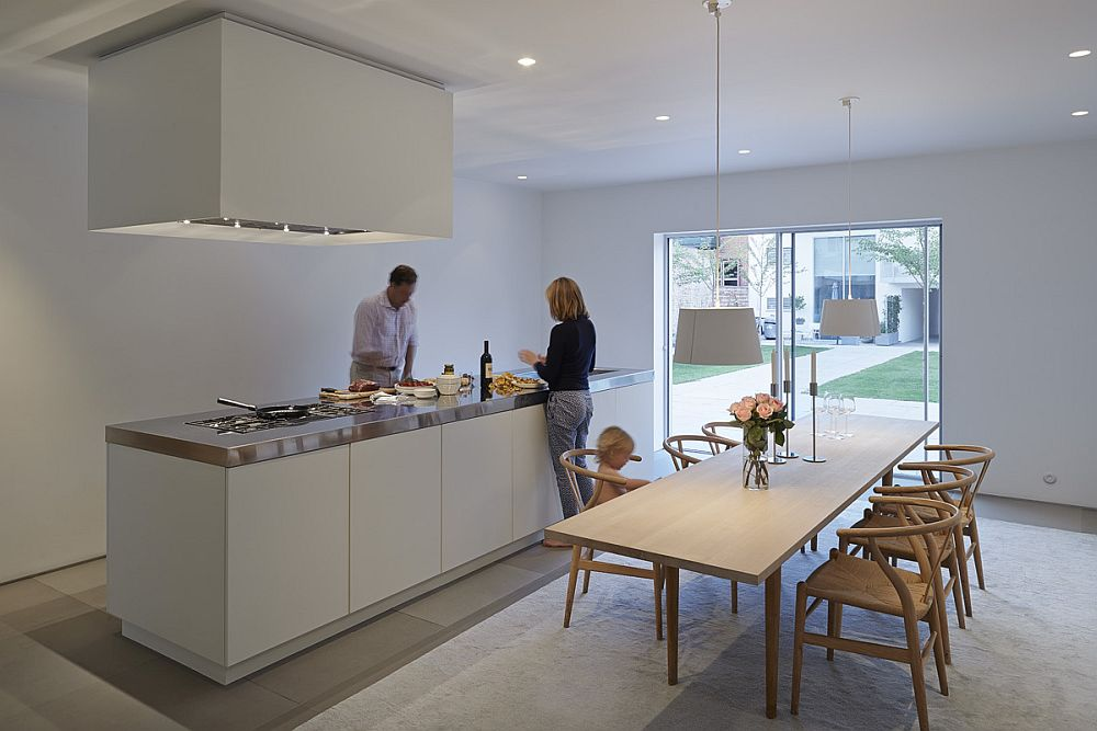 Kitchen and dining area in white connected with the courtyard
