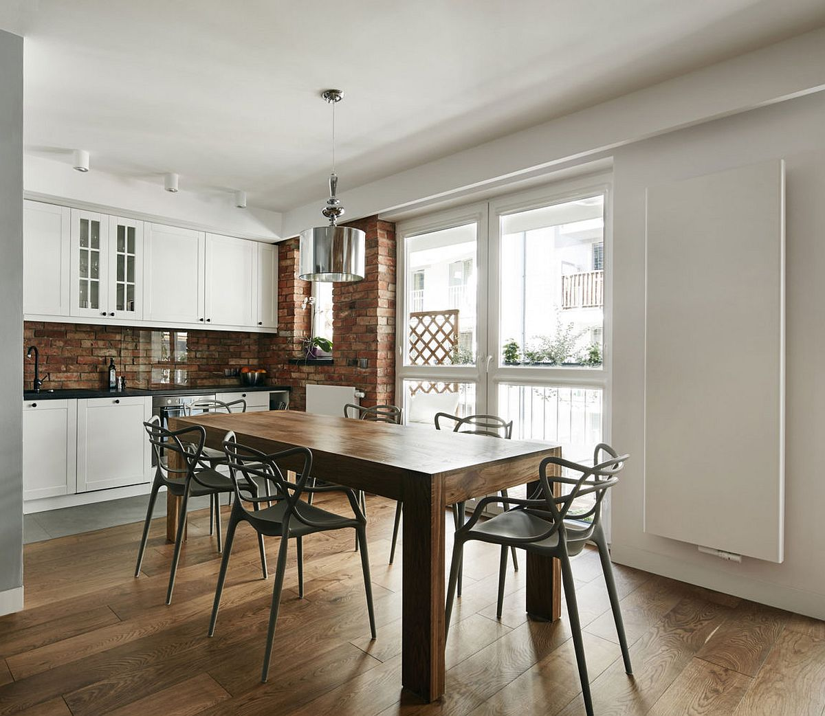 Kitchen and dining area rolled into one inside the small Krakow apartment