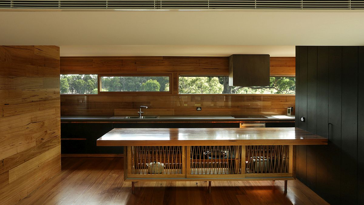 Kitchen in wood with a window into the garden outside