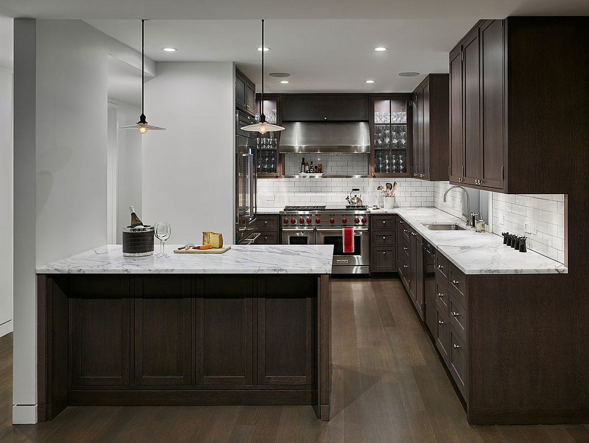 Marble countertops combined with dark wood shelves in the kitchen