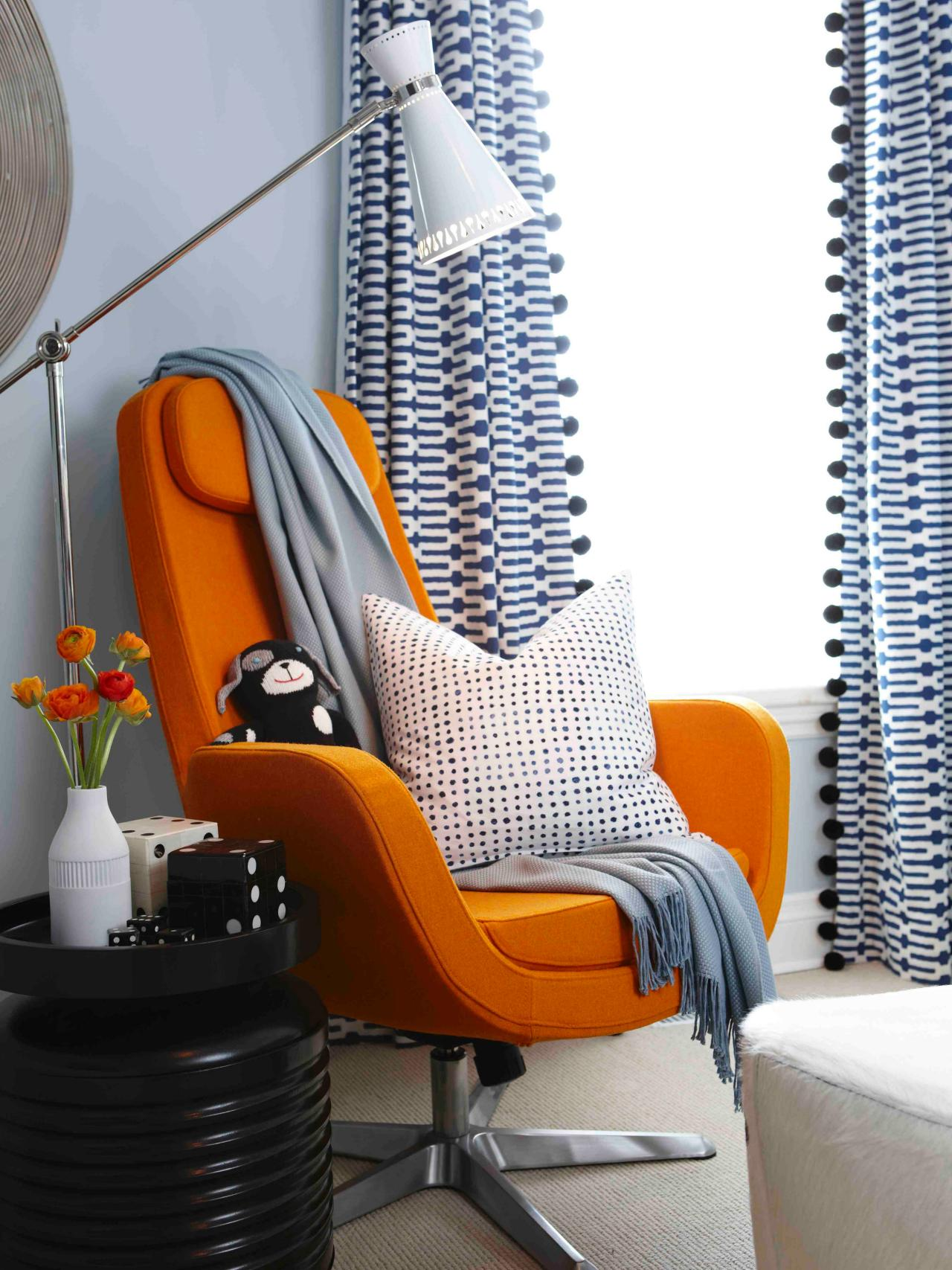 Minimalist reading nook with a vibrant orange chair