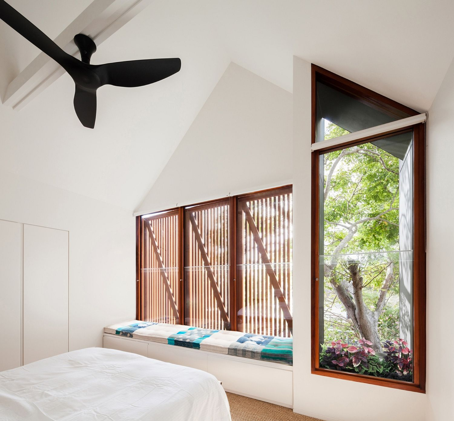 Modern bedroom in white withwindow seat and wooden slat windows