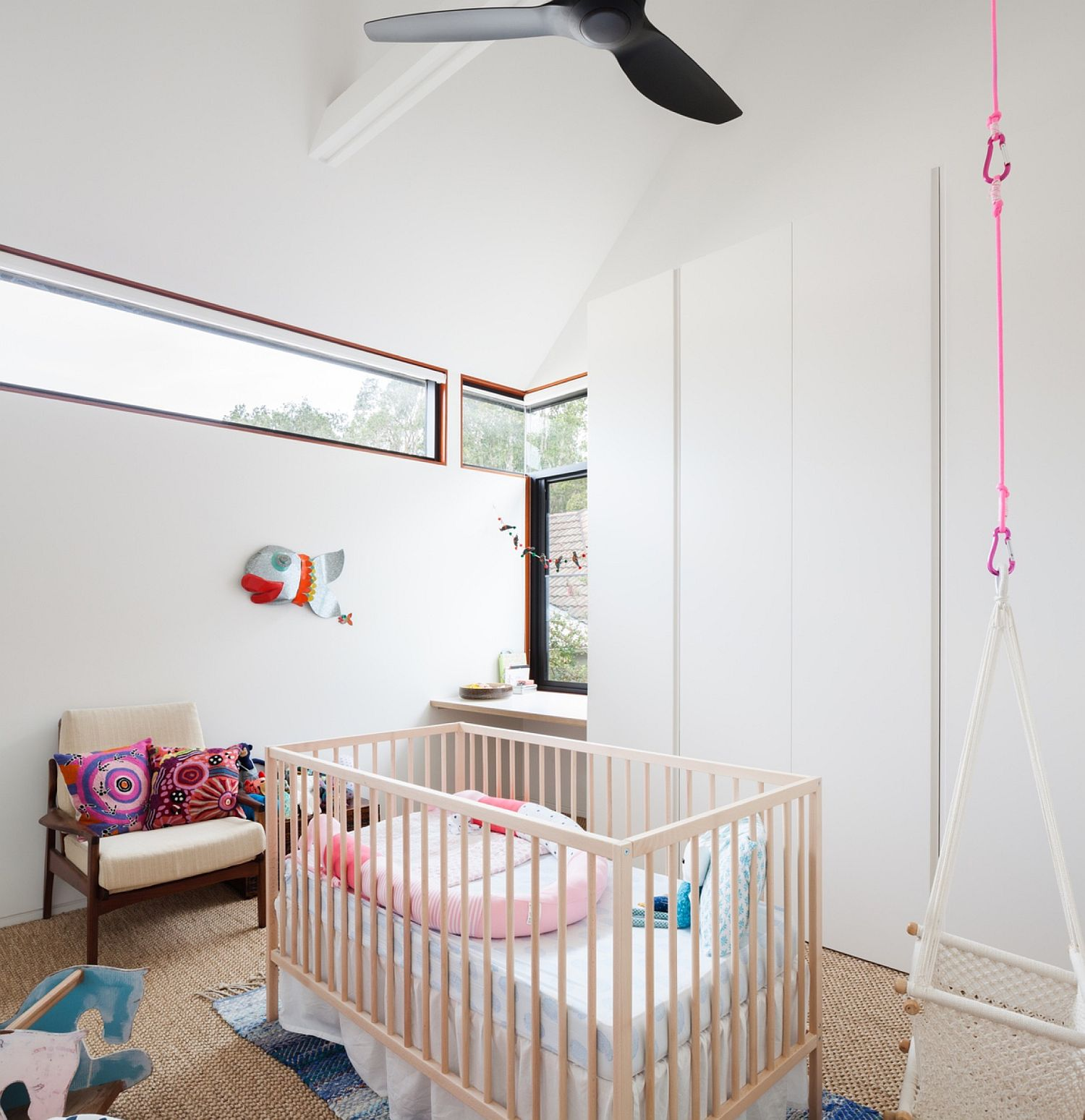 Modern nursery in white with gabled ceiling and ample natural light