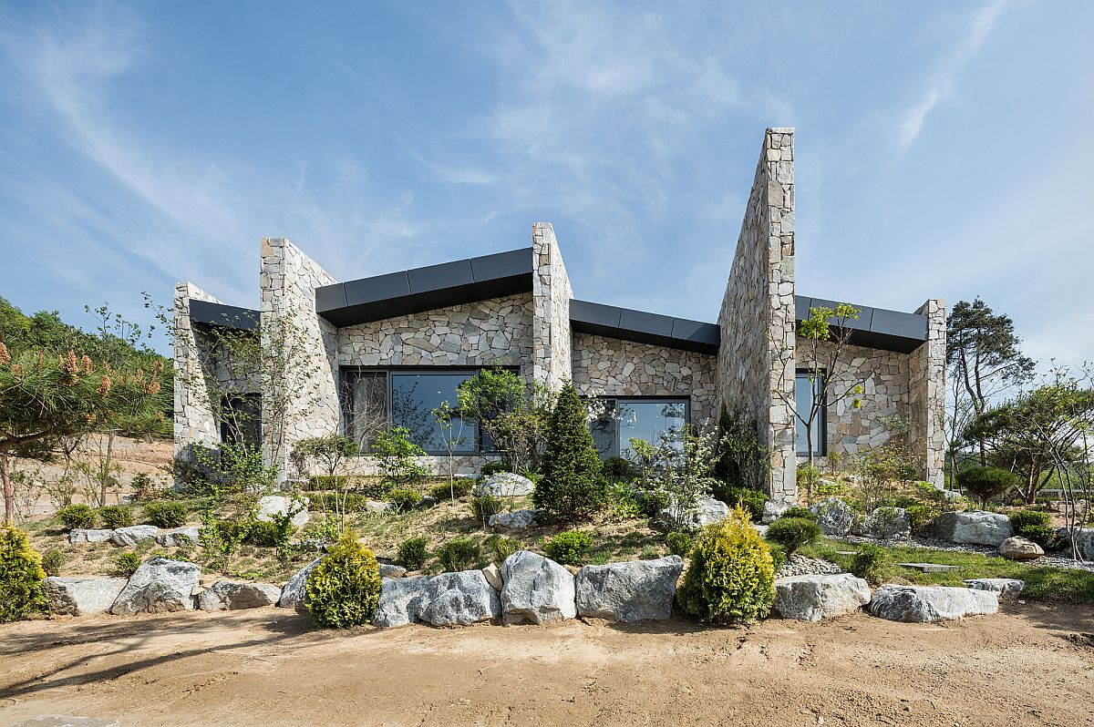 Natural stone combined with glass windows creates a distinctive facade The Layers: Serene Rustic Retreat with Stone Walls Blends into the Landscape