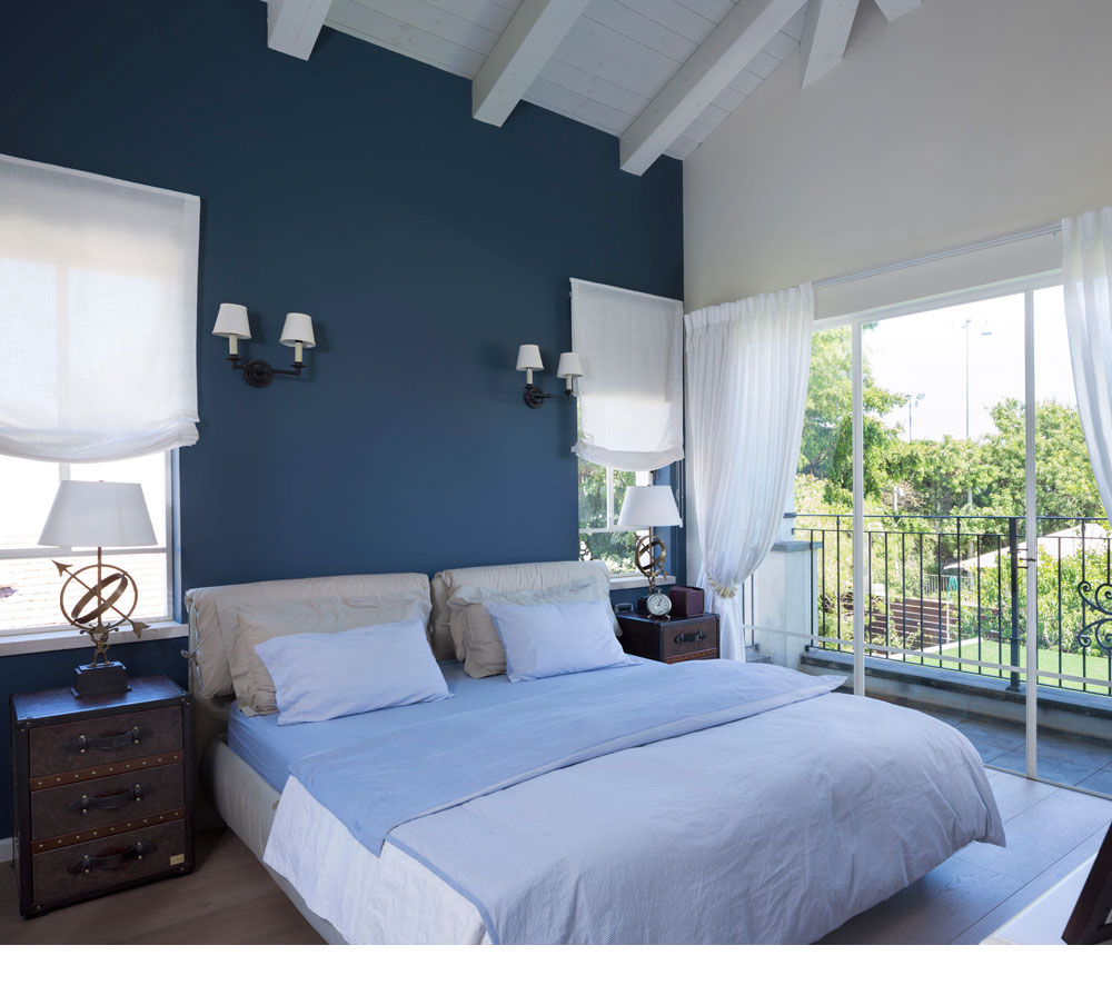 Open blue bedroom with a dark charisma