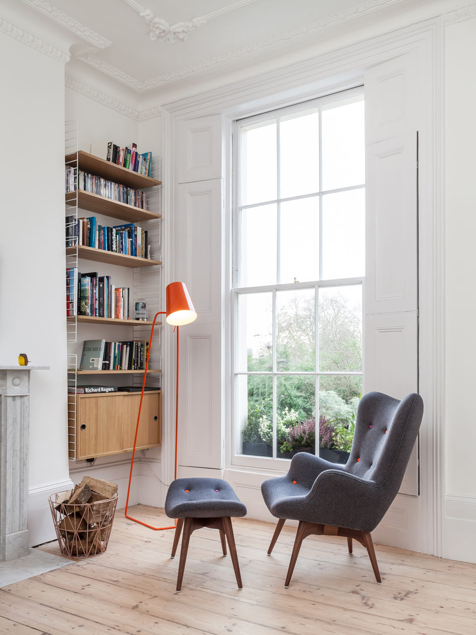 Reading nook with a dynamic reading chair and contemporary lamp