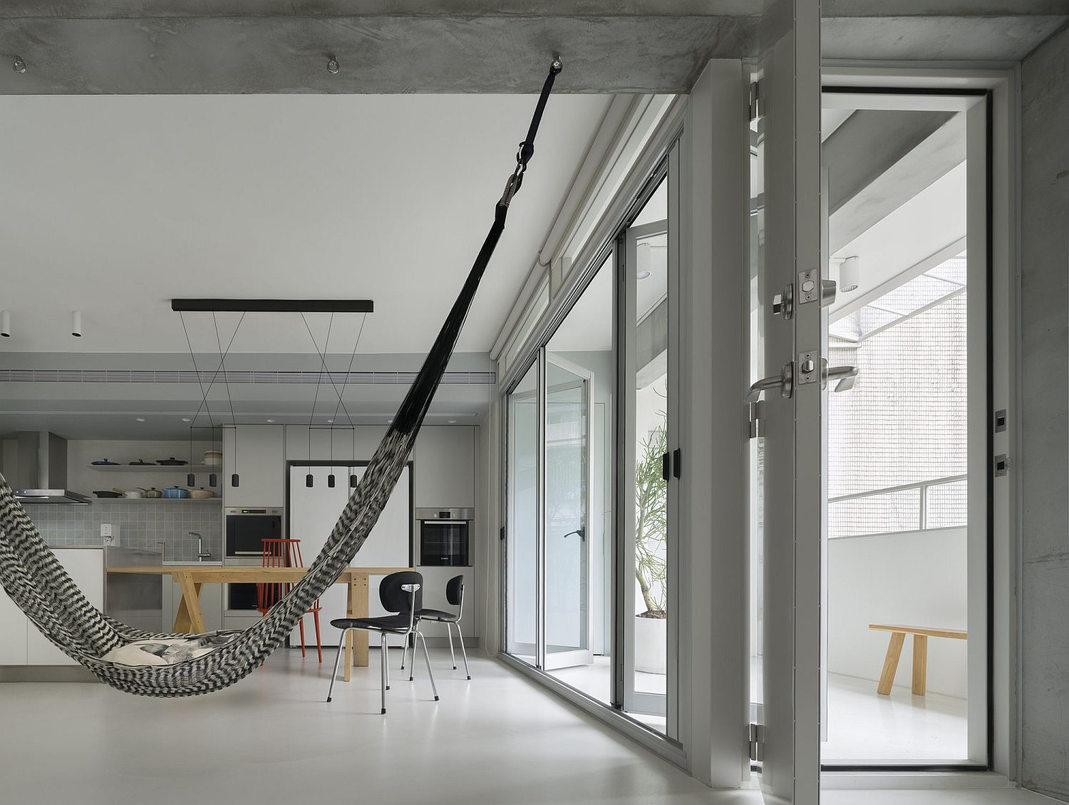 Series of folding glass doors connect the interior with the small balcony