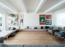 Sleek floating wooden shelf and colorful wall art inside the chic living space 217x155 This Radiant Makeover of 1930's Lisbon Apartment Relies on White and Light!