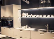 White-kitchen-cabinets-floating-shelves-with-LED-strip-lighting-and-gray-background-217x155