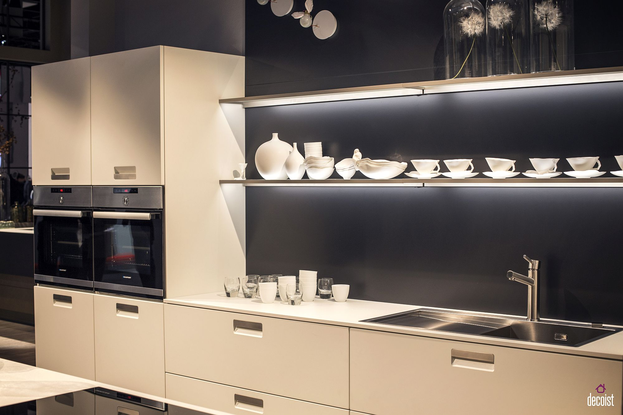 White kitchen cabinets, floating shelves with LED strip lighting and gray background